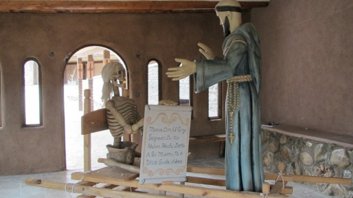 Sister Death holds a placard toward St. Francis's outstretched arms